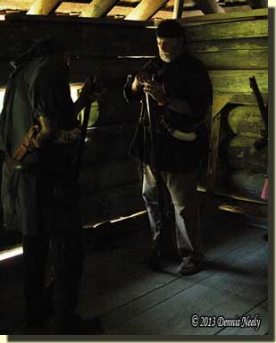 A traditional woodsman reloads in the fort's darkness.