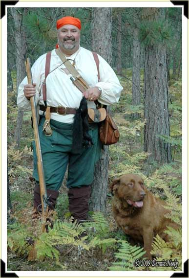 A traditional woodsman and his dog with a black squirrel.