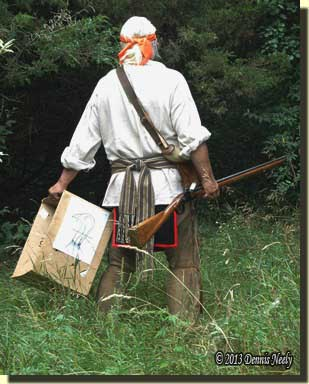 The traditional woodsman leaving the road and heading downhill, carrying the target box and his Northwest gun.