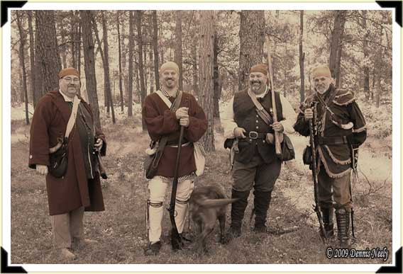 Four traditional woodsmen pause before a morning's simple pursuits. Left to right: Rick Evans, Jeff Nieman, Radar, Jon Bertolet, Norm Blaker. Swamp Hollow, 1760s.