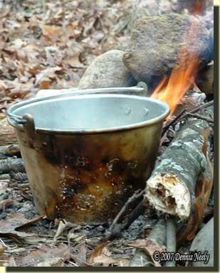 A No. 0 brass kettle warming in an open fire.