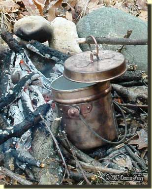 A copper kettle with water boiling in a open fire.
