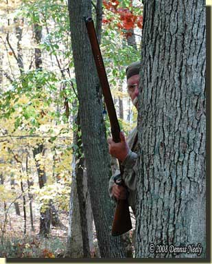 A traditional woodsman concealed behind a oak tree.