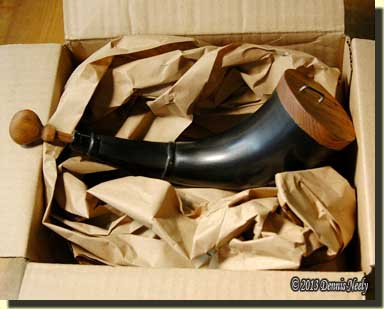 A bison powder horn sitting in the shipping box.