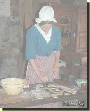 A young woman cutting crusts at Fort Michilimackinac.
