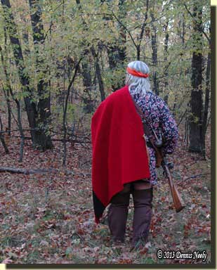 A traditional hunter walking into the fall woods.