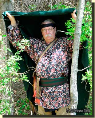 A traditional woodsman pulls a trade blanket up over his head.