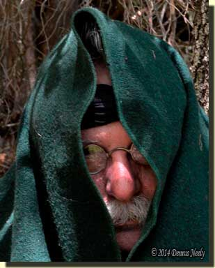A traditional woodsman peering from under a wool trade blanket.