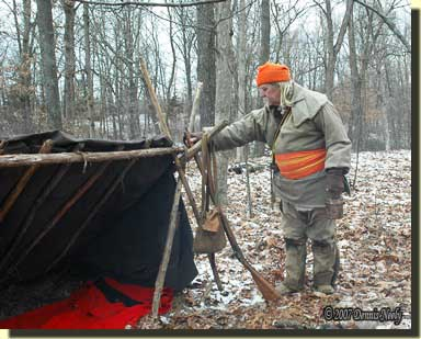 A traditional hunter returns to a lean-to camp.