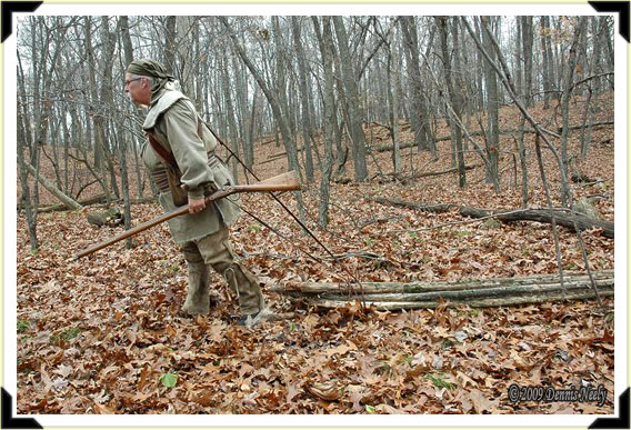 A traditional woodsman pulling a bundle of shelter poles.