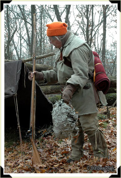 A traditional woodsman bringing a hornet's nest back to camp.