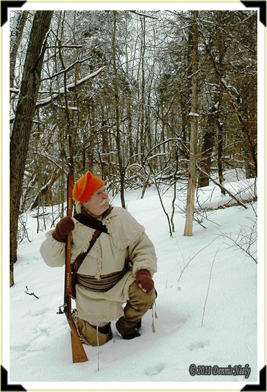 A traditional woodsman kneels in the snow