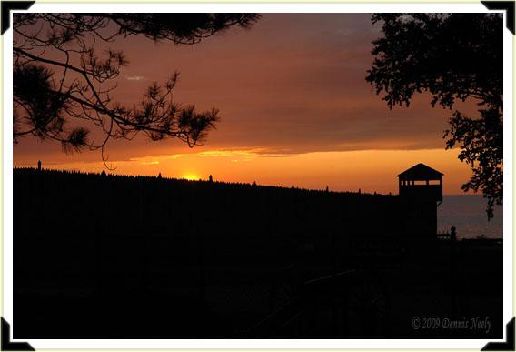 An orange sun setting over Fort Michilimacknac's palisades.