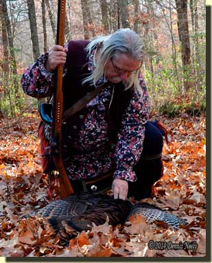 The traditional woodsman kneeling in prayer over a wild turkey.