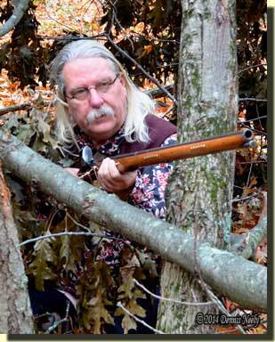 A traditional woodsman sitting within a downed treetop.