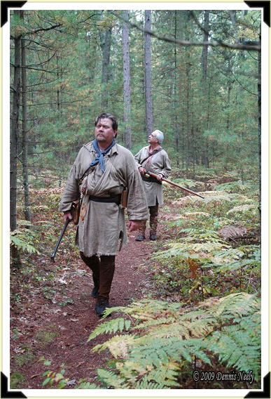 Two traditional woodsman explore a forest trail.
