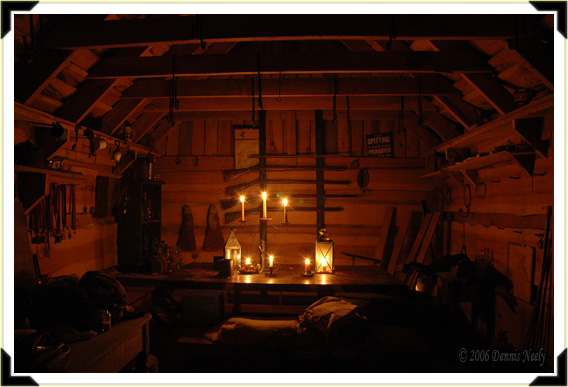 The candle-lit inside of a log cabin.