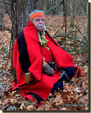 A traditional woodsman sits wrapped in a scarlet trade blanket.