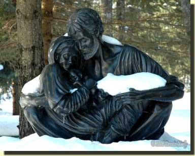 A statue of the Holy Family covered with snow.