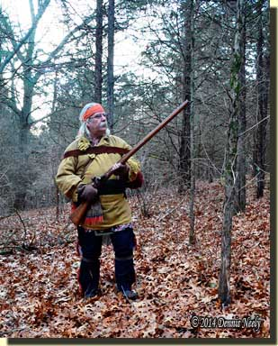 A traditional woodsman moving slow through crunchy oak leaves.