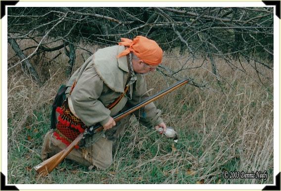 A traditional woodsman picks up a downed bobwhite quail
