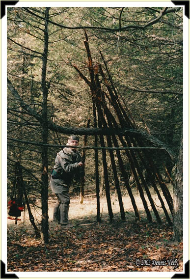 A traditional woodsman setting a rafter pole on a new woodland shelter.