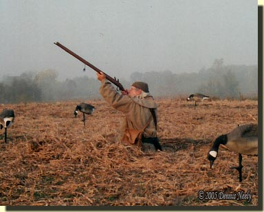 A traditional woodsman sits up in a soy bean field adn takes aim.