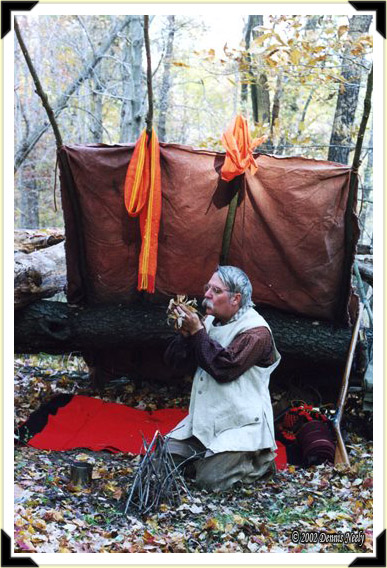 A traditional woodsman blows on a glowing ember in a handful of dry leaves.