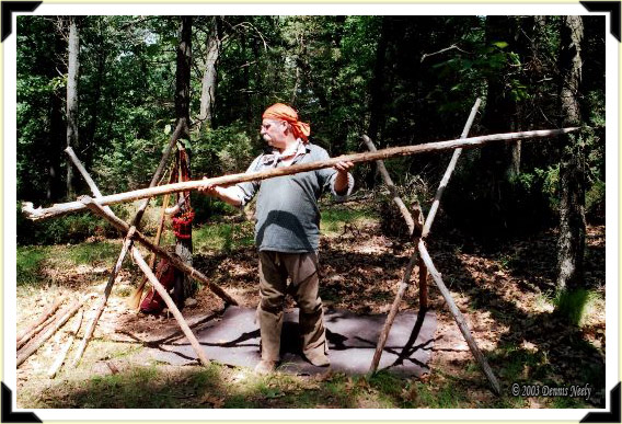 A traditional woodsman lays a red cedar ridge pole for a hunting camp lean-to.