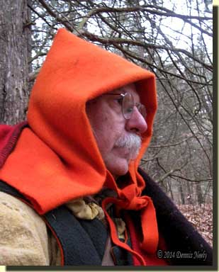 A traditional woodsman wearing a hunter-orange Ojibwe-style hood.