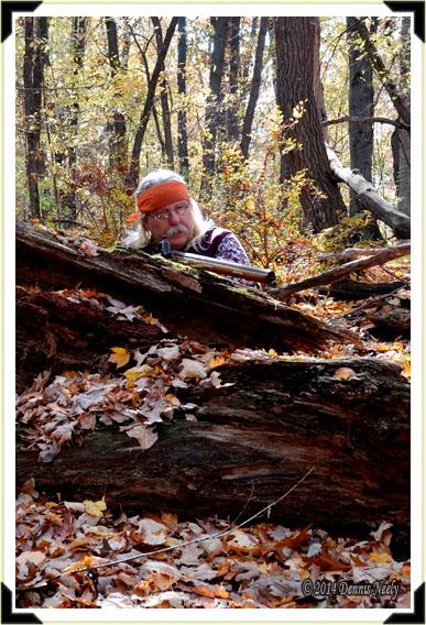 A traditional woodsman hidden behind a downed oak tree.