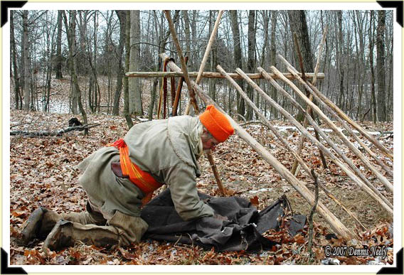 A traditional woodsman folds the canoe tarp that covered his humble shelter.