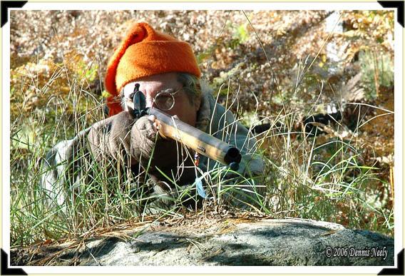 A traditional woodsman aims his Northwest trade gun from behind a large boulder.