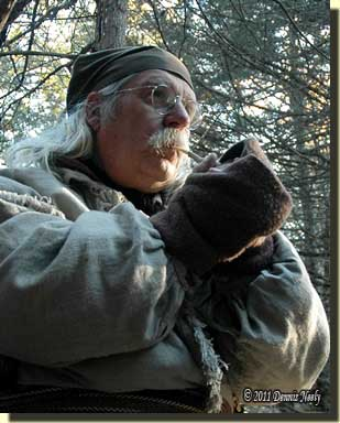 A traditional woodsman using a wing-bone turkey call.