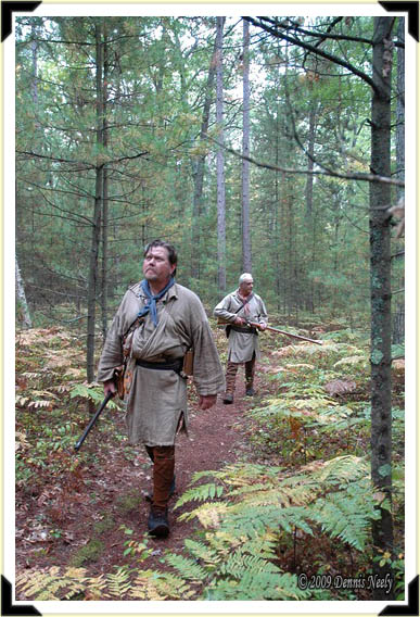 Two traditional woodsmen scouting a woodland trail.