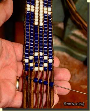 Weaving antique blue beads between brain-tanned thongs.
