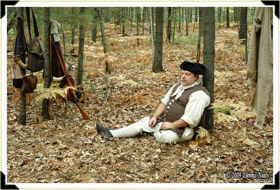 A War for Independence re-enactor sitting against a tree in the forest.