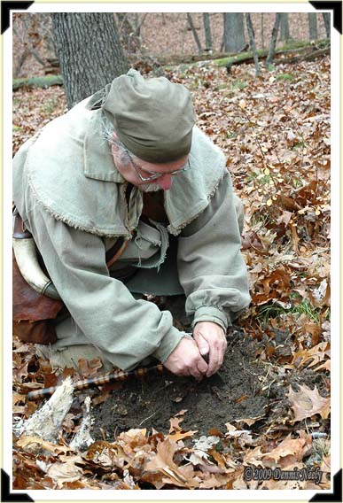 A traditional woodsman using a tomahawk to dig a hole.