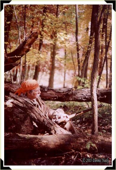 A traditional woodsman, half-hidden in a windfall, waits on a fox squirrel to close the distance.