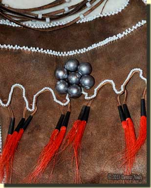 Seven trade gun balls on an Odawa-style shot pouch.