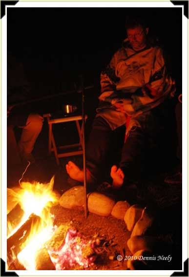 A traditional woodsman warming his feet by the fire.