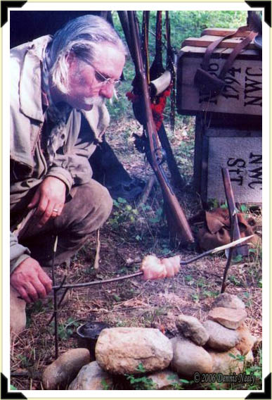 A traditional woodsman roasting a fowl's breast over an open fire.
