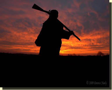 A 18th-century woodsman walks into the woods at sunrise.