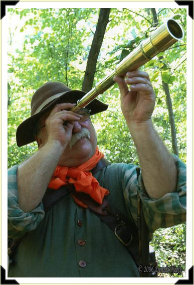An 18th-century traditional woodsman looking through a brass telescope.