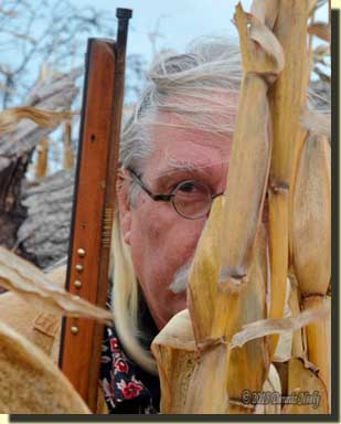 A returned Native captive hunter peer from behind a row of cornstalks.