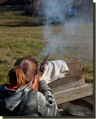 A young lady firing a Jacob Dickert-style flintlock rifle.
