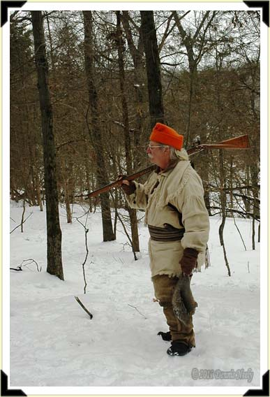 A traditional hunter with a gray squirrel looks to the east.
