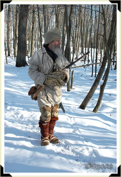 A French woodsman stands in a snowy forest.