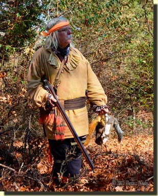 A traditional woodsman carrying two squirrels pauses and looks north.