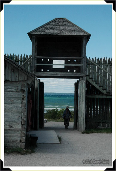 A dejected voyageur walks through the water gate at Fort Michilimackinac